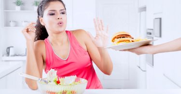 woman eating salad refusing burger, no cheat day