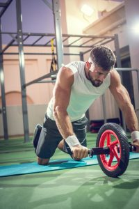 fit man doing wheel rollout