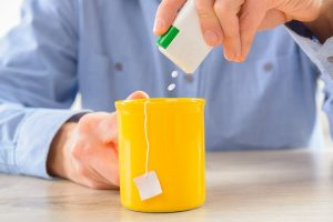 man pouring artificial sweetener tablets into cup of tea