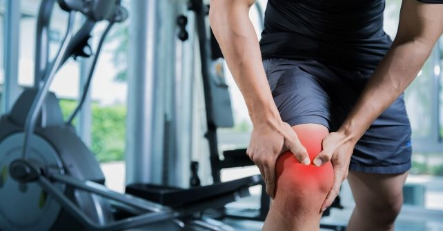 man in pain holding injured knee and thigh in gym