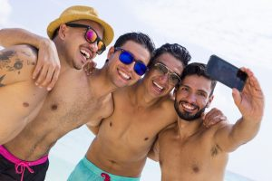 group of gay men taking selfie on beach, friends