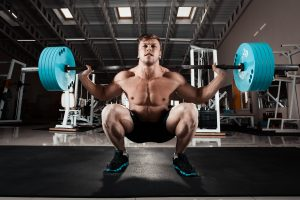 fit man lifting barbell while doing squats in gym
