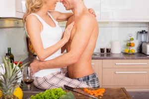 couple getting intimate on kitchen counter, vegetable on chopping board