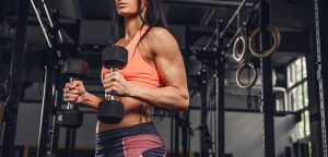 fit athletic woman lifting dumbbells, free weights