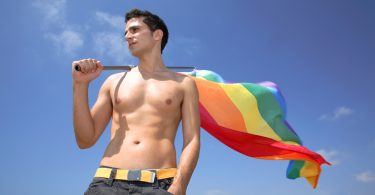 shirtless man holding rainbow flag, lgbtq