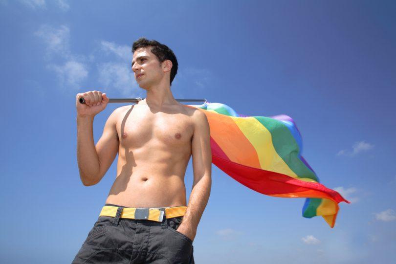 shirtless man holding rainbow flag, lgbtq
