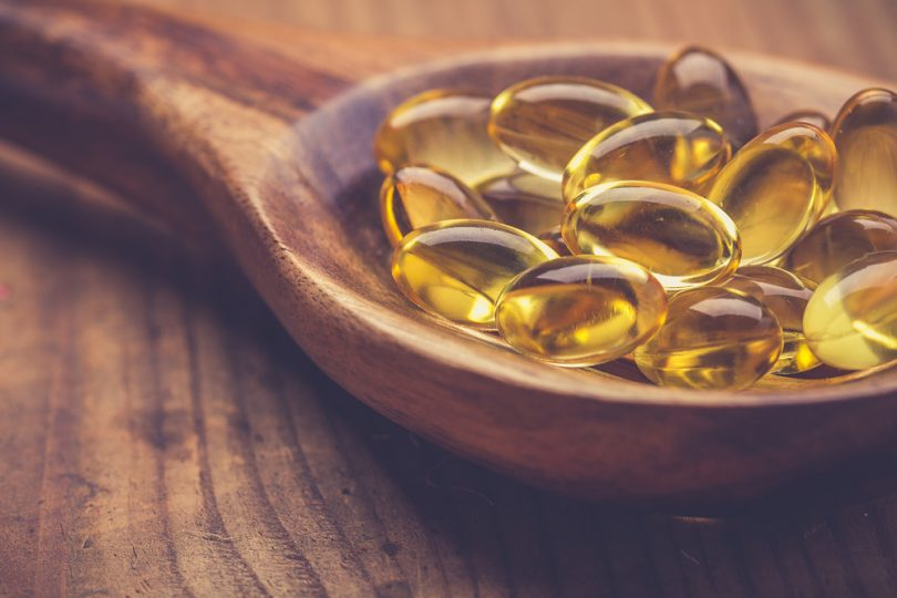 omega 3 supplement on wooden spoon