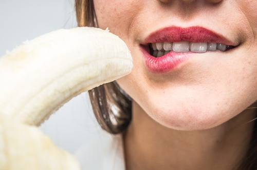 woman holding peeled banana, biting lower lip