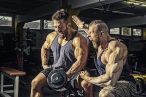 trainer pushing man to extreme workout and lifting in gym