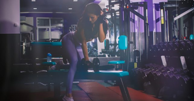fit woman in gym holding dumbbells