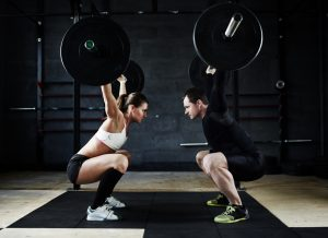 athletic couple doing overhead squats with heavy barbell