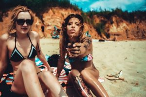 women in bikini smoking cannabis weed on beach