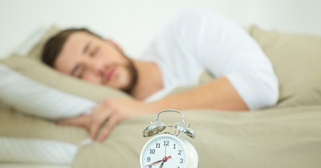 man sleeping with alarm clock in foreground