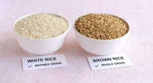 white and brown rice in bowls, refined and whole grain