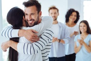 man hugging woman showing appreciation with friends in background