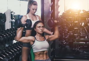 female gym trainer assisting fit woman with weight training, dumbbells