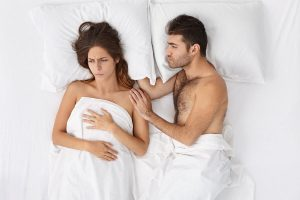 couple in bed, woman mad at apologizing husband