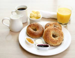 breakfast bagel with jam and butter, juice and coffee