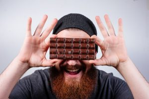 bearded guy holding chocolate bar against face and happy with Progentra