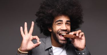 Afro guys who uses Progentra biting into chocolate and holding ok sign