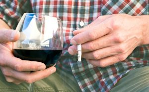 man holding wine and cigarette learning about Progentra to help with erectile dysfunction