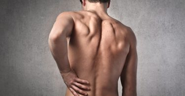shirtless man holding his lower back experiencing pain