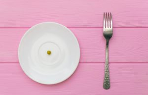 a single pea on plate with fork on the side is an extreme diet