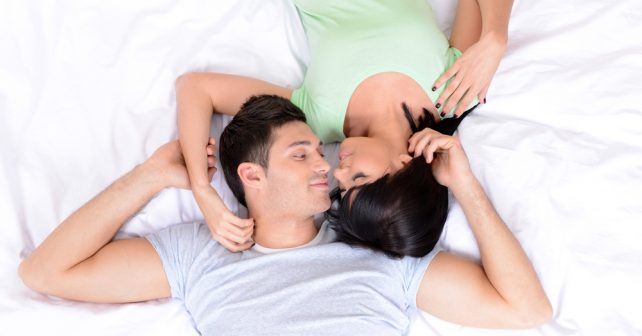 man and woman laying in bed